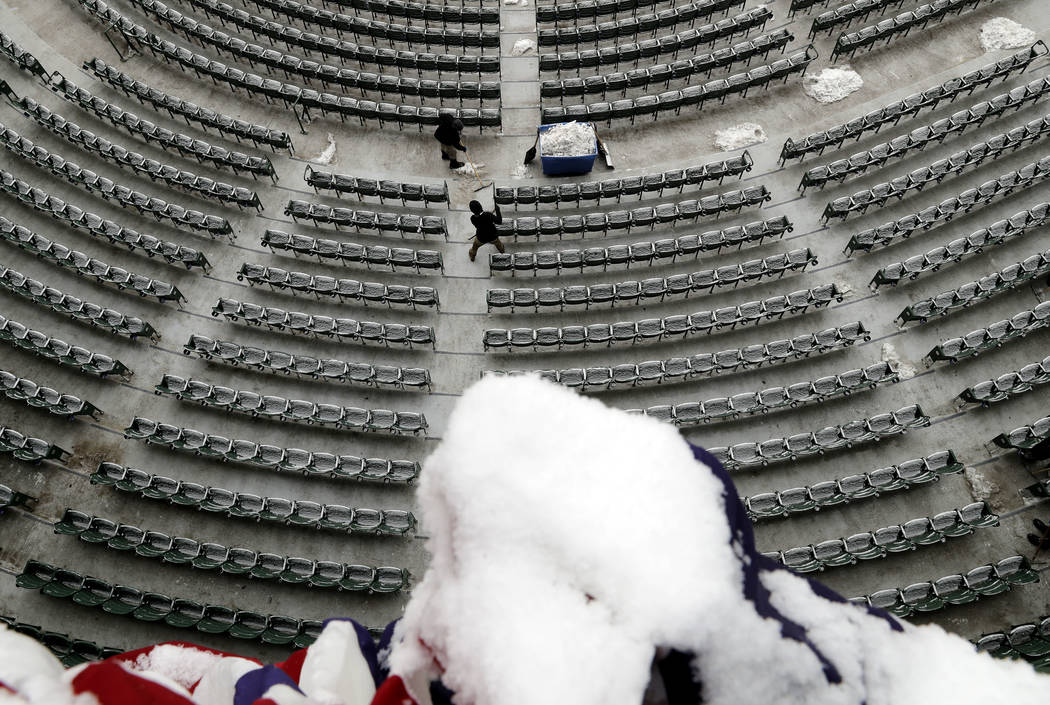 Workers clear snow at Wrigley Field in Chicago, Monday, April 9, 2018. The Chicago Cubs game against the Pittsburgh Pirates was postponed a day because of persistent snow that covered much of Wrig ...