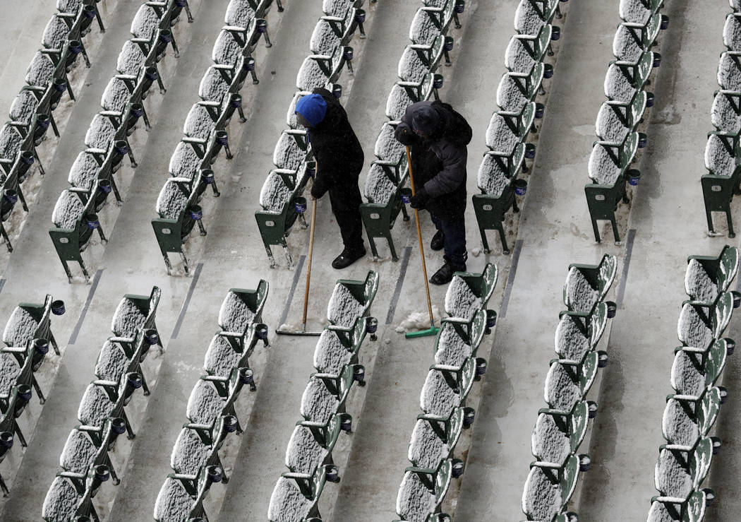 Workers at Wrigley Field clear snow before the Chicago Cubs home-opener baseball game against the Pittsburgh Pirates, in Chicago. The Cubs' game against the Pirates was postponed a day because of  ...