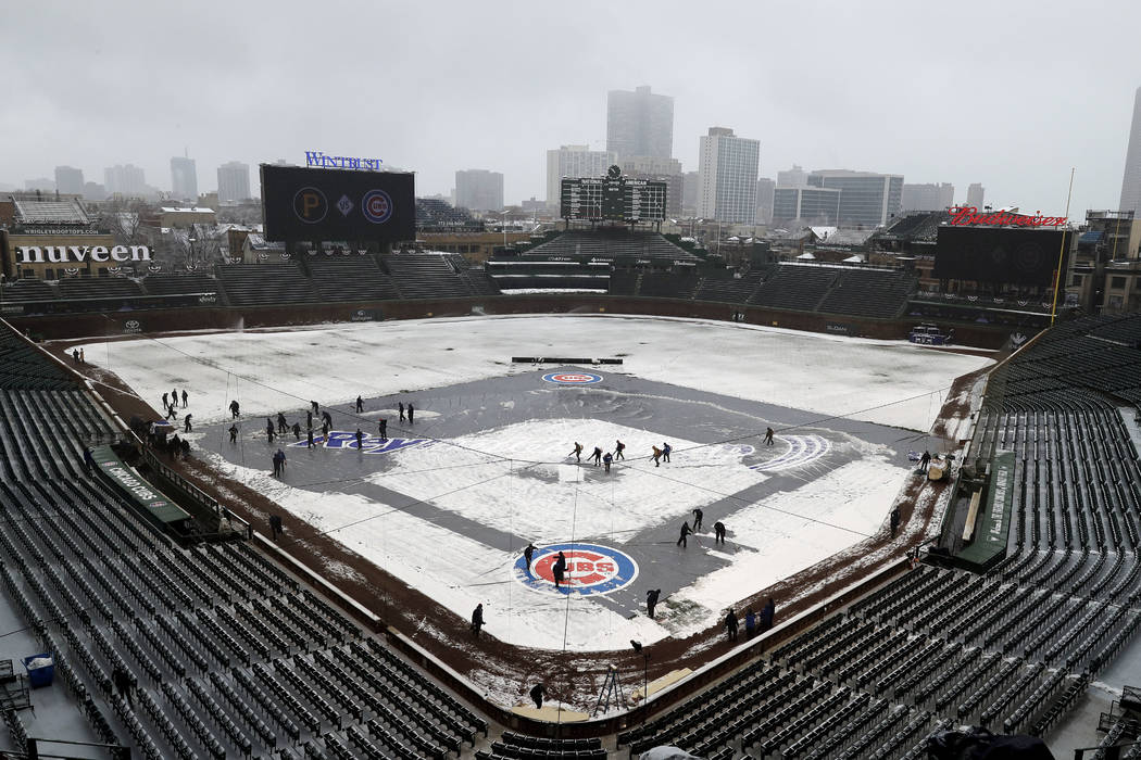 Members of the grounds crew clear snow at Wrigley Field in Chicago, Monday, April 9, 2018. The Cubs' game against the Pittsburgh Pirates was postponed a day because of persistent snow that covered ...
