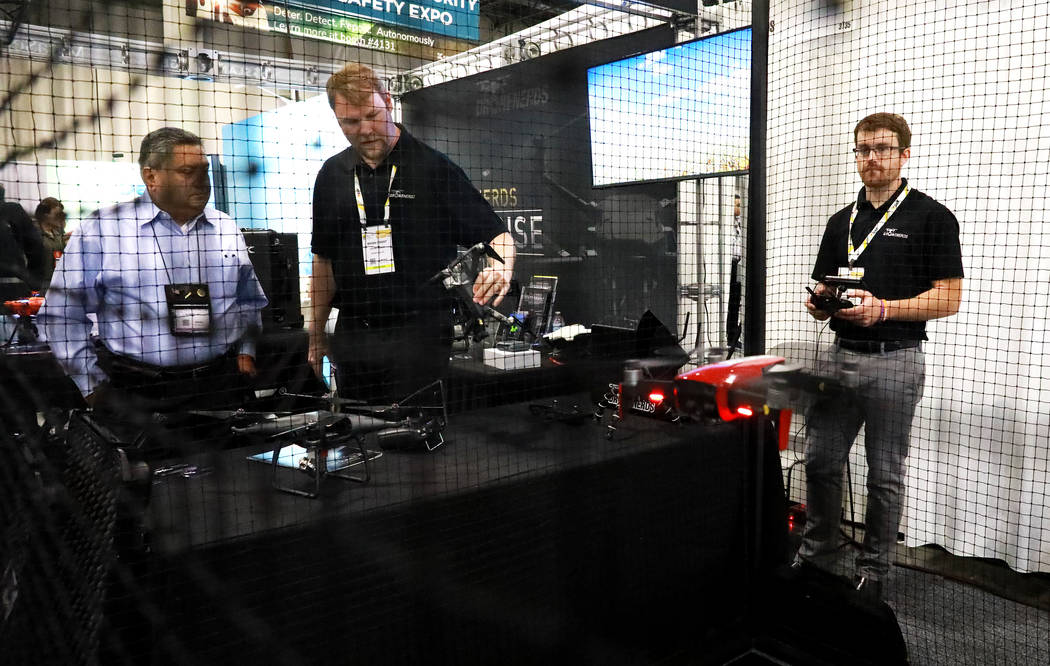 Brian Grant, of Drone Nerds, center, talks to Henry Olivarez, of Arizona, about a Mavic Pro while Austin Gibson flies a Mavic Air during the International Security Conference & Exposition, als ...