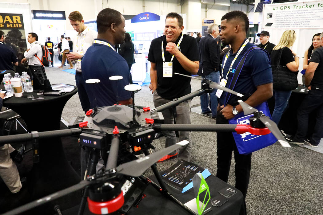 Mark Buffington talks to Kendrick Julmis, left, and Leonard Jeffers, both from Florida, about the Aptomony Blackhawk during the International Security Conference & Exposition, also known as IS ...
