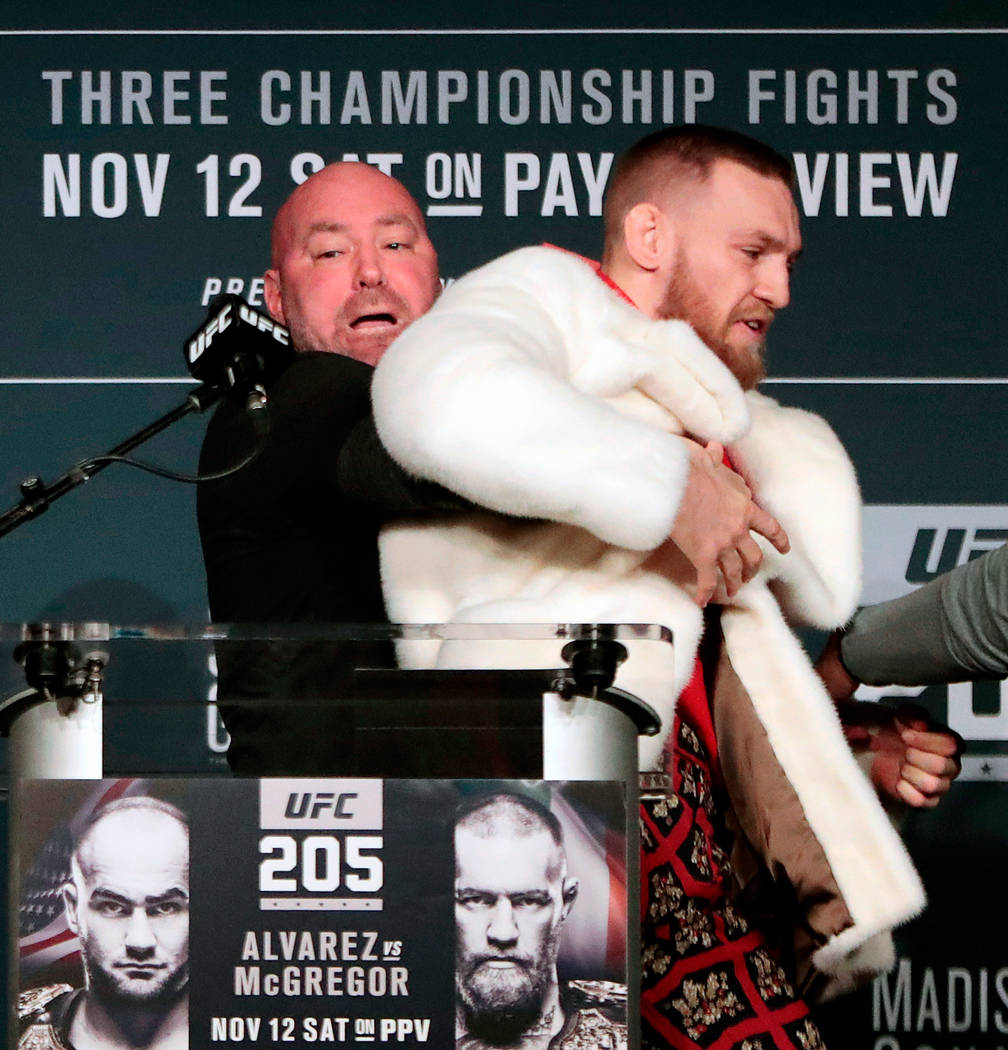 FILE - In this Nov. 10, 2016, file photo, fighter Conor McGregor, right, is restrained by UFC president Dana White during a news conference ahead of the UFC 205 mixed martial arts fight between Mc ...