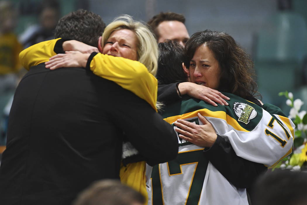 Mourners comfort each other as people attend a vigil at the Elgar Petersen Arena, home of the Humboldt Broncos, to honor the victims of a fatal bus accident in Humboldt, Saskatchewan on Sunday, Ap ...