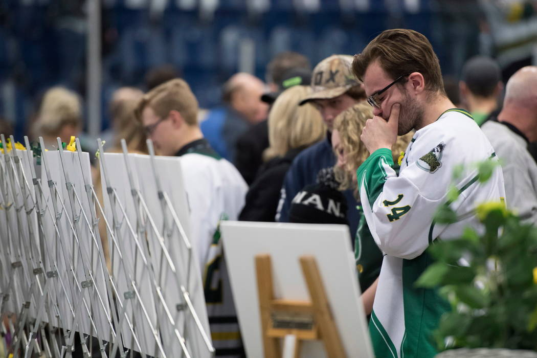 People react as they look at photos of the victims during a vigil at the Elgar Petersen Arena, home of the Humboldt Broncos, to honor the victims of Friday's fatal bus accident, in Humboldt, Saska ...