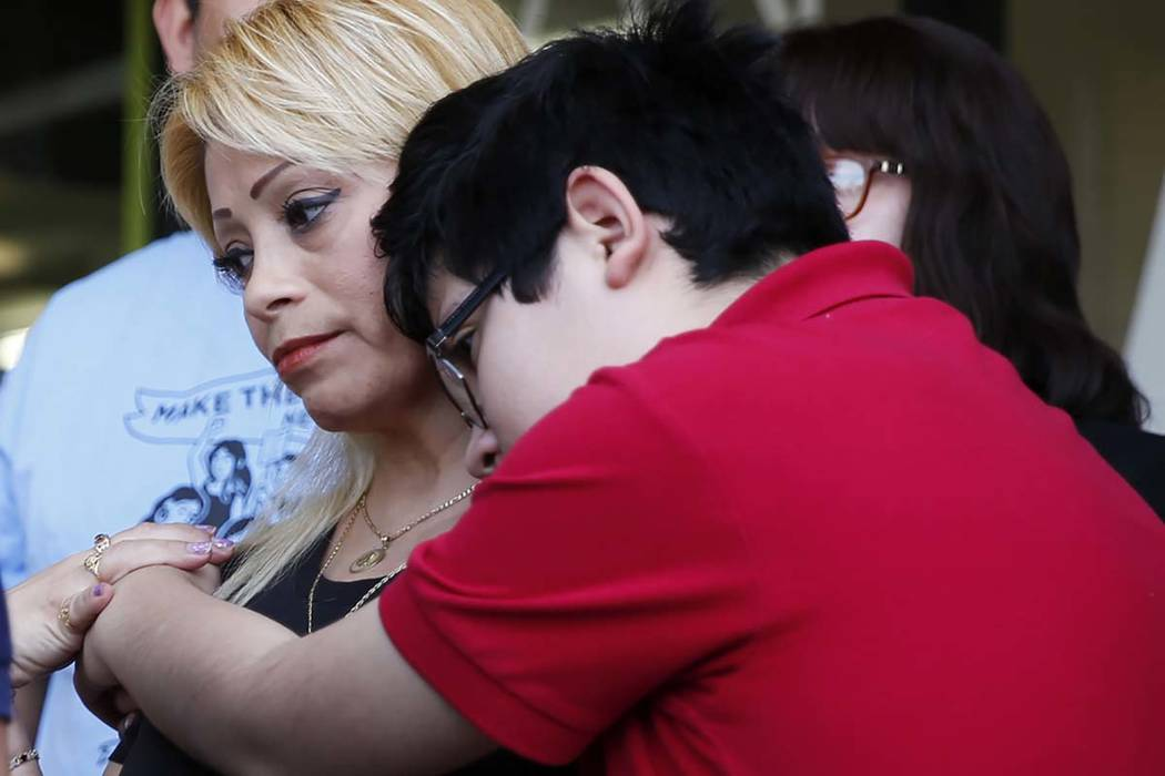 Cecilia Gomez, who was detained by Immigration and Customs Enforcement, is embraced by her son Eric Avelar-Gomez, 13, after describing her experience with ICE during a news conference at The Las V ...