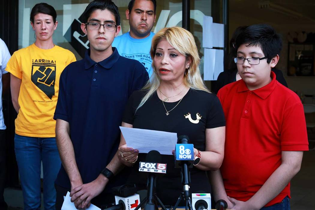 Cecilia Gomez, who was detained by Immigration and Customs Enforcement, reads a statement with her sons Ricardo Avelar-Gomez, 18, left, and Eric, 13, by her side during a news conference at The La ...