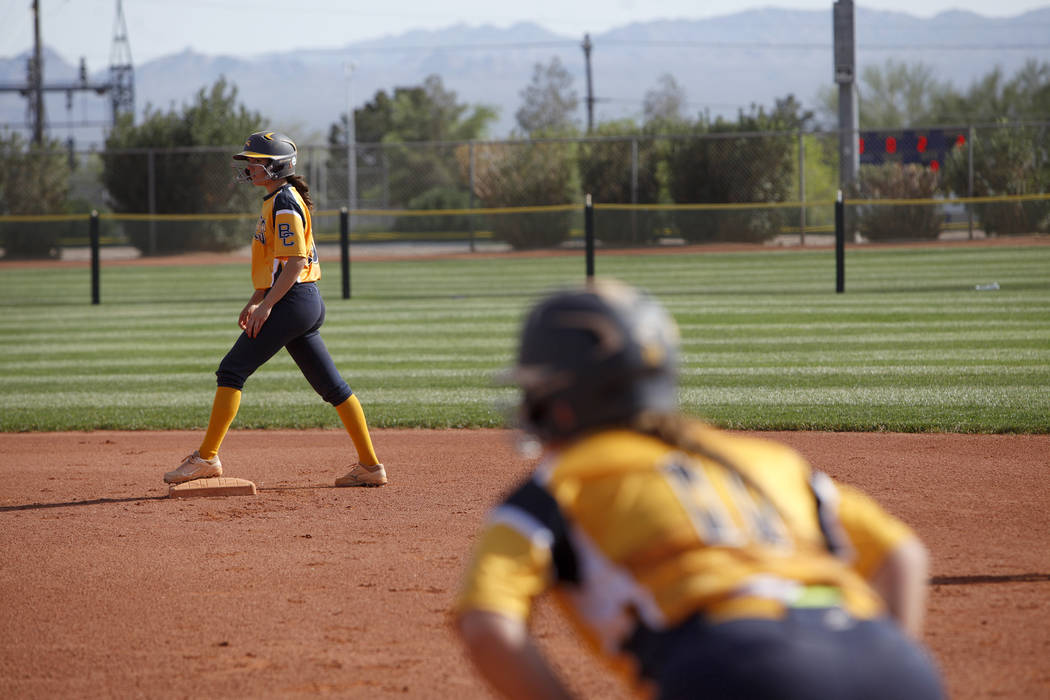 Jordan Moorhead (10) waits to run to third as teammate Lily Ofman (11) anticipates the next hit at a softball game against Virgin Valley in Boulder City, Monday, April 9, 2018. Rachel Aston Las Ve ...