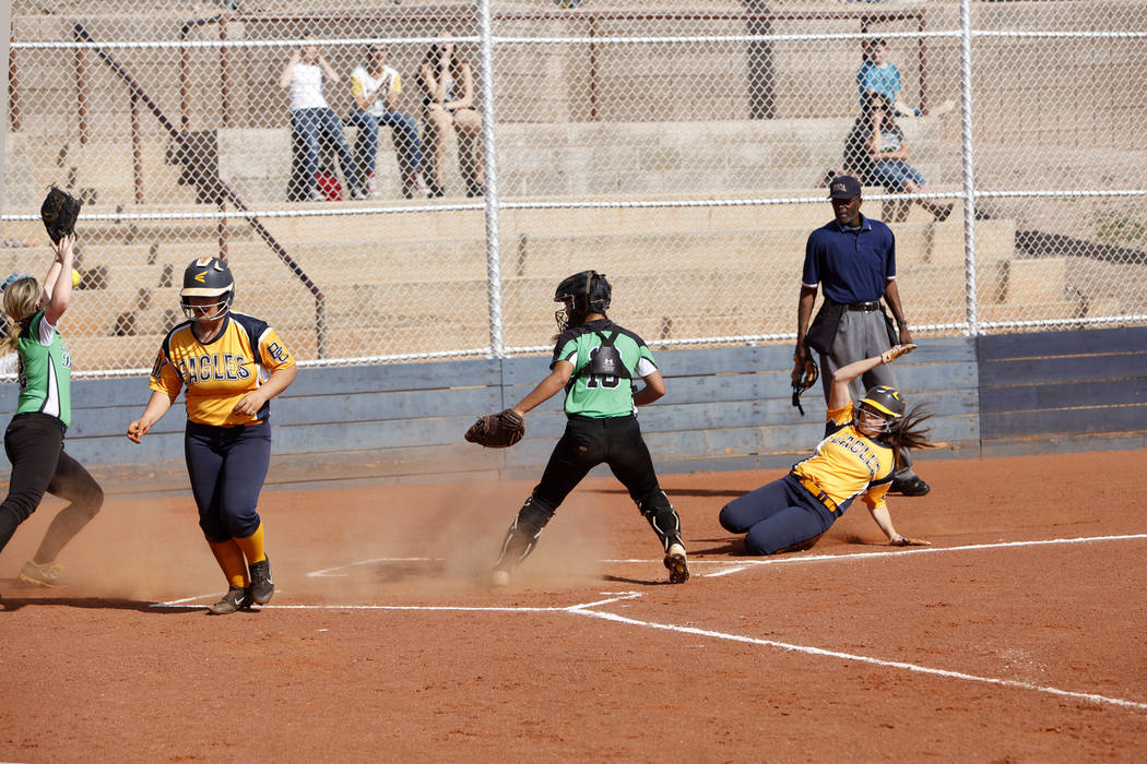 Lily Ofman (11) makes a run as her teammate Rose Mackey (5) lands a run after her as Virgin Valley's Taylor Barnum reaches for the ball as catcher Kaysha Heath (18) watches on at a softball game i ...