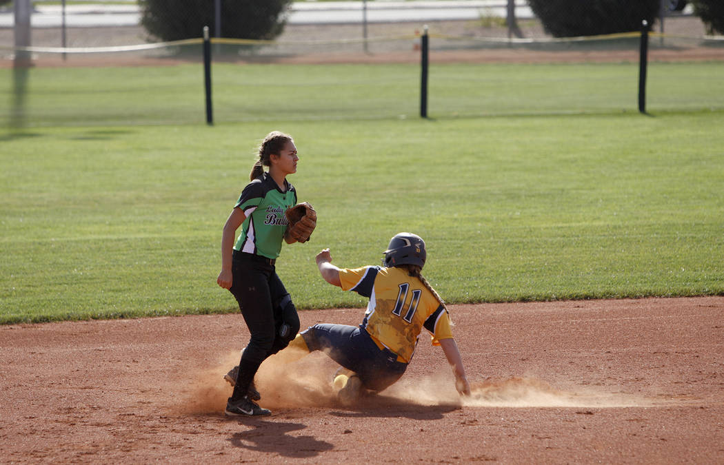 Boulder City High School's Lily Ofman (11) slides to second plate as Virgin Valley High School's Karyme DeSantiago watches for the ball at a softball game in Boulder City, Monday, April 9, 2018. R ...