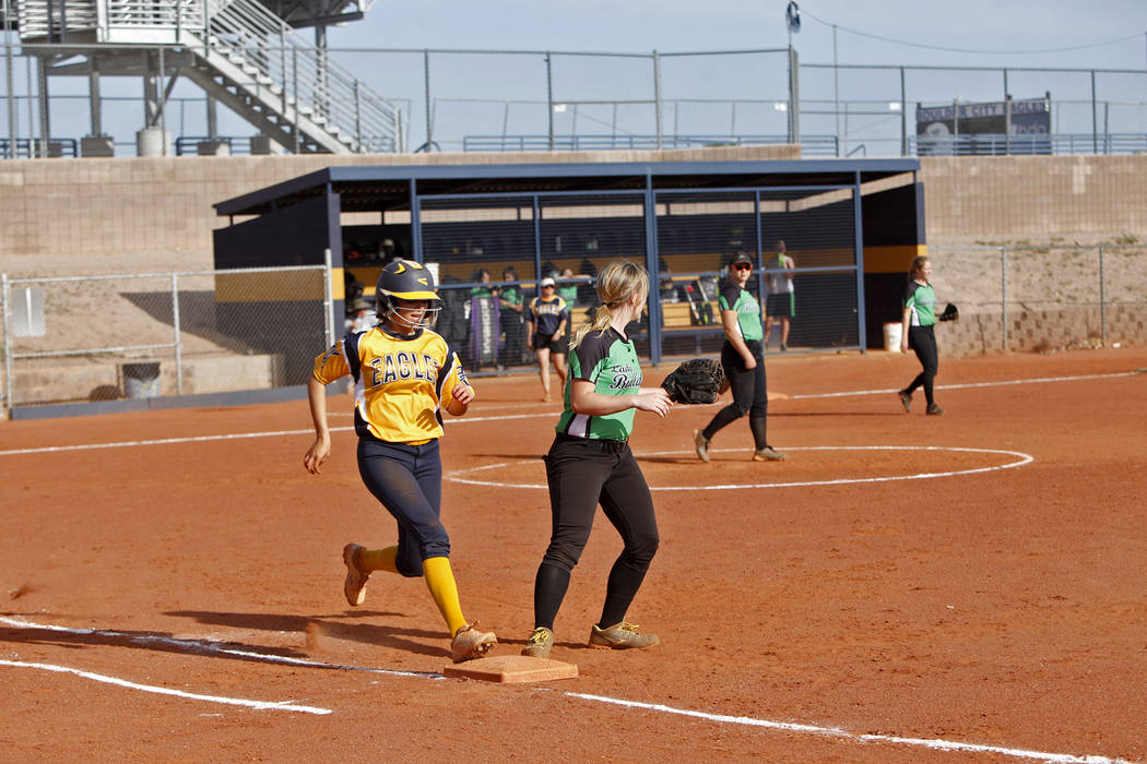 Boulder City High School's Jordan Moorhead (10) runs to first base safely as  Virgin Valley High School's Taylor Barnum (12) at a softball game in Boulder City, Monday, April 9, 2018. Rachel Aston ...