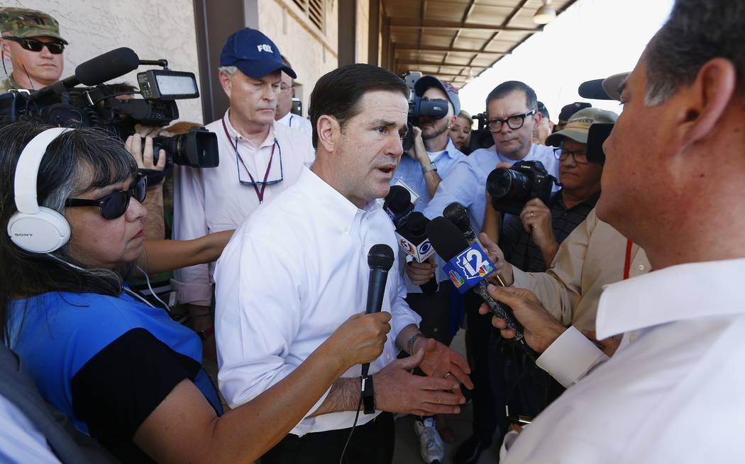 Arizona Gov. Doug Ducey, center, speaks with the media after meeting with the Arizona National Guard prior to their deployment to the Mexico border at the Papago Park Military Reservation Monday,  ...