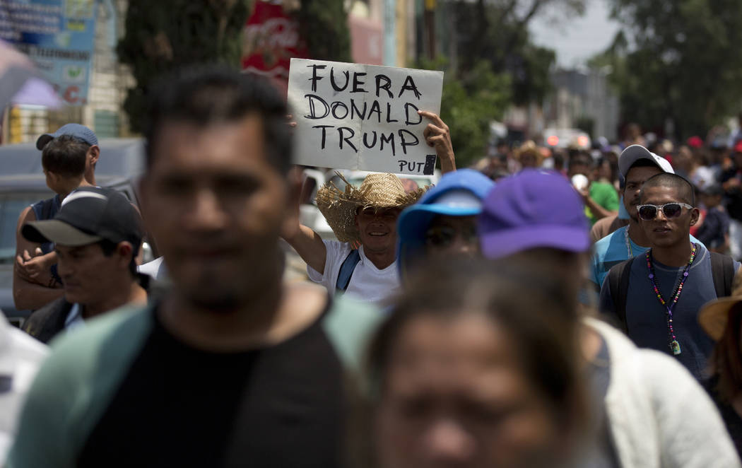 "Central American migrants who participated in the annual Migrants Stations of the Cross caravan, one with a sign that says in Spanish: ""Get out Donald Trump,"" walk to the Basilica of Gua ..."