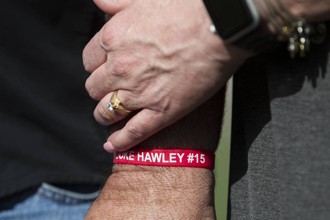 Aaron Hawley, wearing a wristband with the name of her daughter Brooke, holds hands with his wife Rhonda, during a press conference announcing the Brooke Hawley Memorial Scholarship, at the Bettye ...