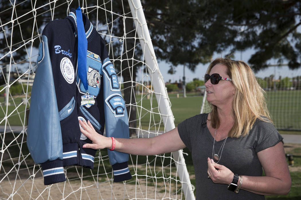 Rhonda Hawley touches the letterman jacket of her daughter Brooke, during a press conference announcing a memorial scholarship named after Brooke, at the Bettye Wilson Soccer Complex in Las Vegas, ...