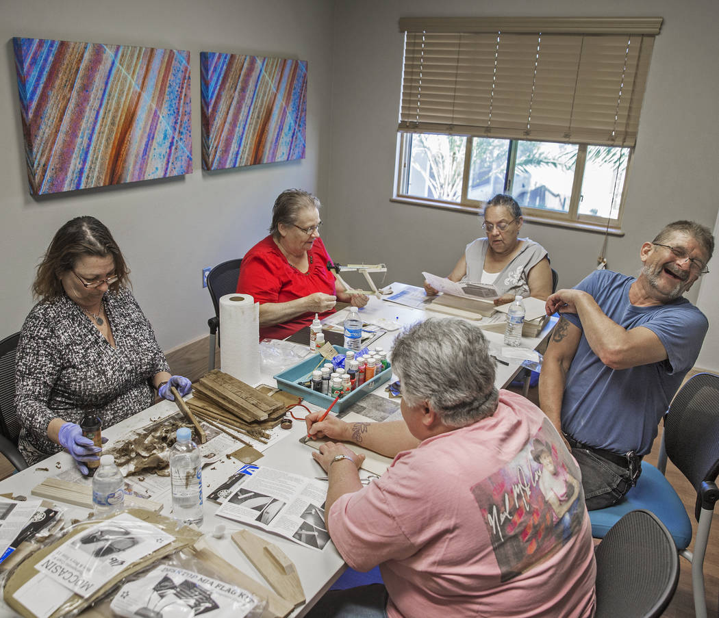 Clyda Byrd-Lopez, left, Carol Ambrose, Debbie Lara, William Bryant and Michele Marshall socialize while building shoe shine boxes on Tuesday, April 17, 2018, at Patriot Place Apartments, in Las Ve ...