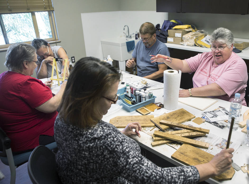 Michele Marshall, right, William Bryant, Debbie Lara, Carol Ambrose and Clyda Byrd-Lopez socialize while building shoe shine boxes on Tuesday, April 17, 2018, at Patriot Place Apartments ...
