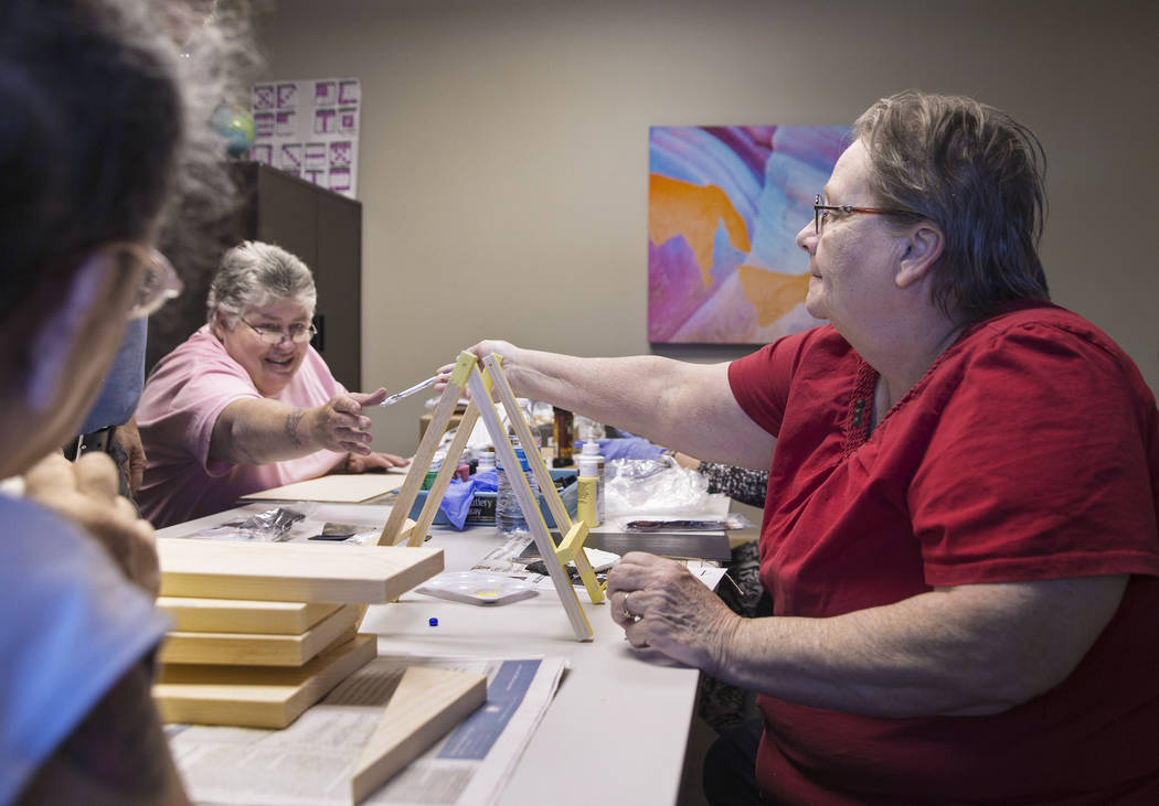 Michele Marshall, left, hands Carol Ambrose a pen while building shoe shine boxes on Tuesday, April 17, 2018, at Patriot Place Apartments, in Las Vegas. Patriot Place Apartments is an affordable h ...