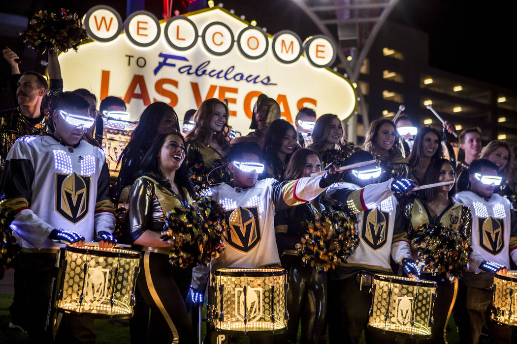 The Knight Line Drumbots and Golden Knights cheerleaders come together for a group photo in front of a scale model Las Vegas sign on Toshiba Plaza outside of T-Mobile Arena on Wednesday, Feb. 28,  ...