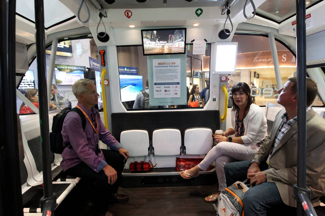 John Zimmer, from left, Carla Legible and Mike Mayfield, of Zimmer Radio & Marketing Group of Columbia, Missouri, watch screens in the Next Gen TV Autonomous Transport during the National Asso ...