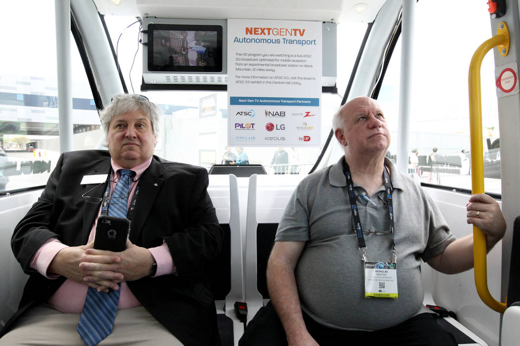 Don Moore of High Point (North Carolina) University, left, and Nicholas Meriage of Creative Digital Masters in Chicago watch screens in the Next Gen TV Autonomous Transport during the National Ass ...