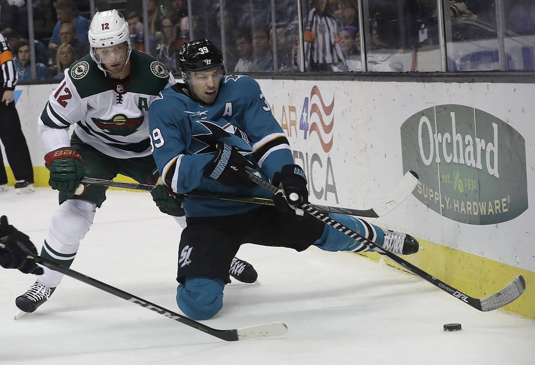 San Jose Sharks center Logan Couture (39) reaches for the puck in front of Minnesota Wild center Eric Staal (12) during the second period of an NHL hockey game in San Jose, Calif., Saturday, April ...