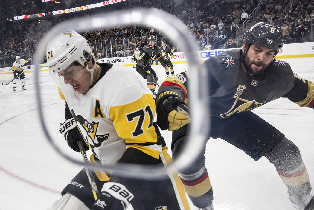 Penguins center Evgeni Malkin (71) fights for the puck with Golden Knights defenseman Deryk Engelland (5) in the second period of Pittsburgh's road matchup with the Golden Knights on Thursday, Dec ...