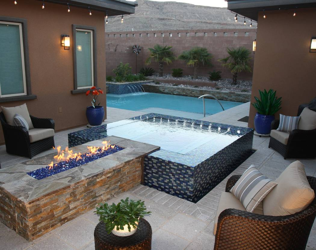Paragon Pools Las Vegas A custom-designed linear firepit with tempered fire glass traverses an all-tile, perimeter overflow spa.