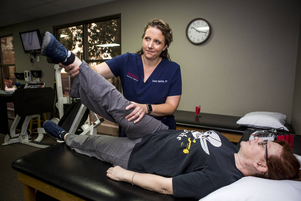 Casey Bartolo, P.T., who worked with several survivors of the Oct. 1 shooting for free, helps Sandra Moncayo with her stretches at Jackson Physical Therapy in Spring Valley on Wednesday, April 11, ...