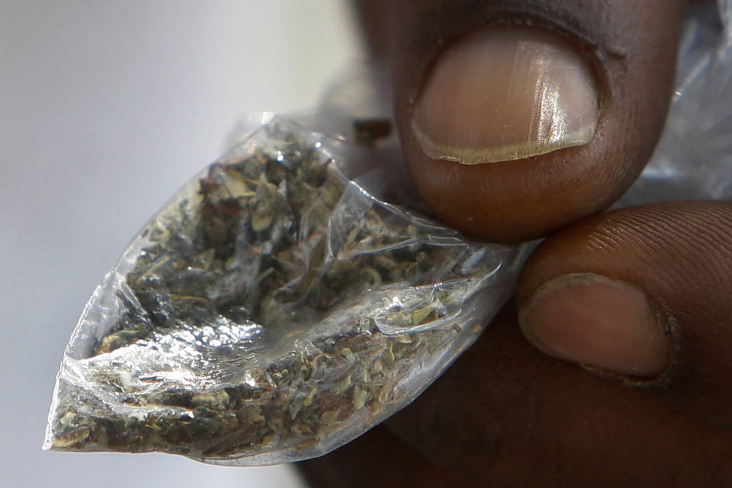 FILE - In this June 29, 2016 file photo, a man holds a bag of synthetic marijuana in Houston. In a report released Tuesday, April 10, 2018, fake marijuana likely contaminated with rat poison has k ...