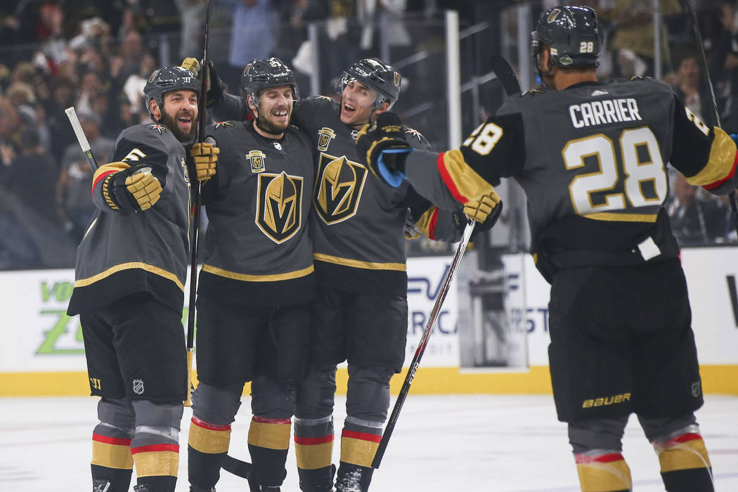 Golden Knights players celebrate a goal by Shea Theodore, second from left, while playing the Los Angeles Kings during the first period of Game 1 of an NHL hockey first round playoff series at T-M ...