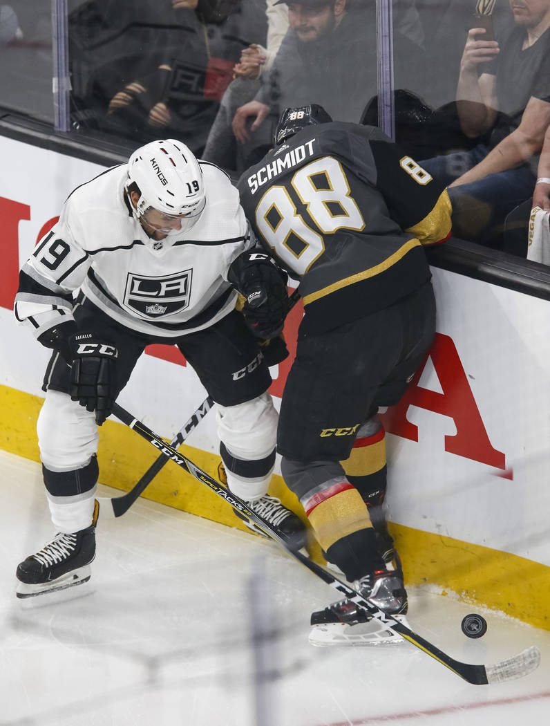 Los Angeles Kings center Alex Iafallo (19) and Golden Knights defenseman Nate Schmidt (88) vie for the puck during the first period of Game 1 of an NHL hockey first-round playoff series at T-Mobil ...