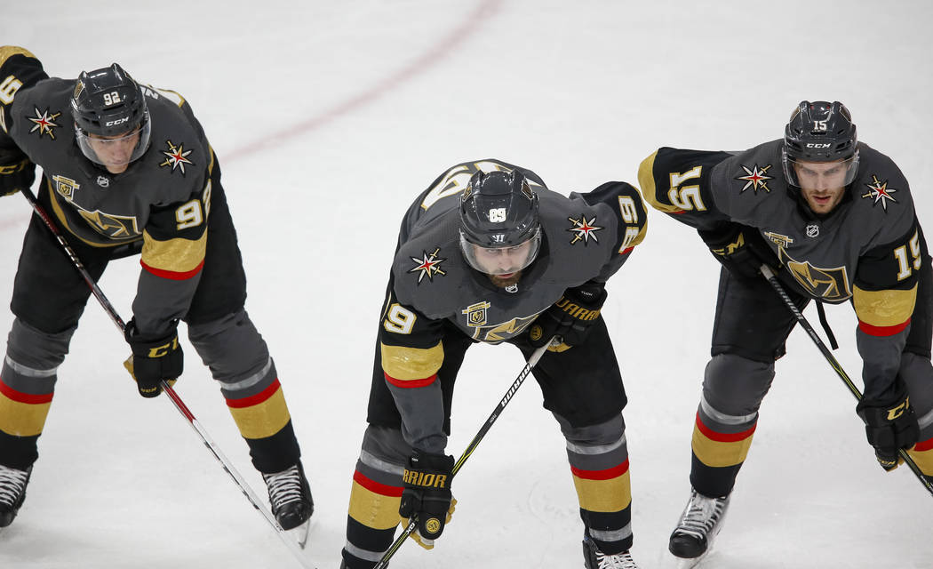 Golden Knights left wing Tomas Nosek (92) right wing Alex Tuch (89) and defenseman Jon Merrill (15) wait for the face-off during the first period of Game 1 of an NHL hockey first-round playoff ser ...