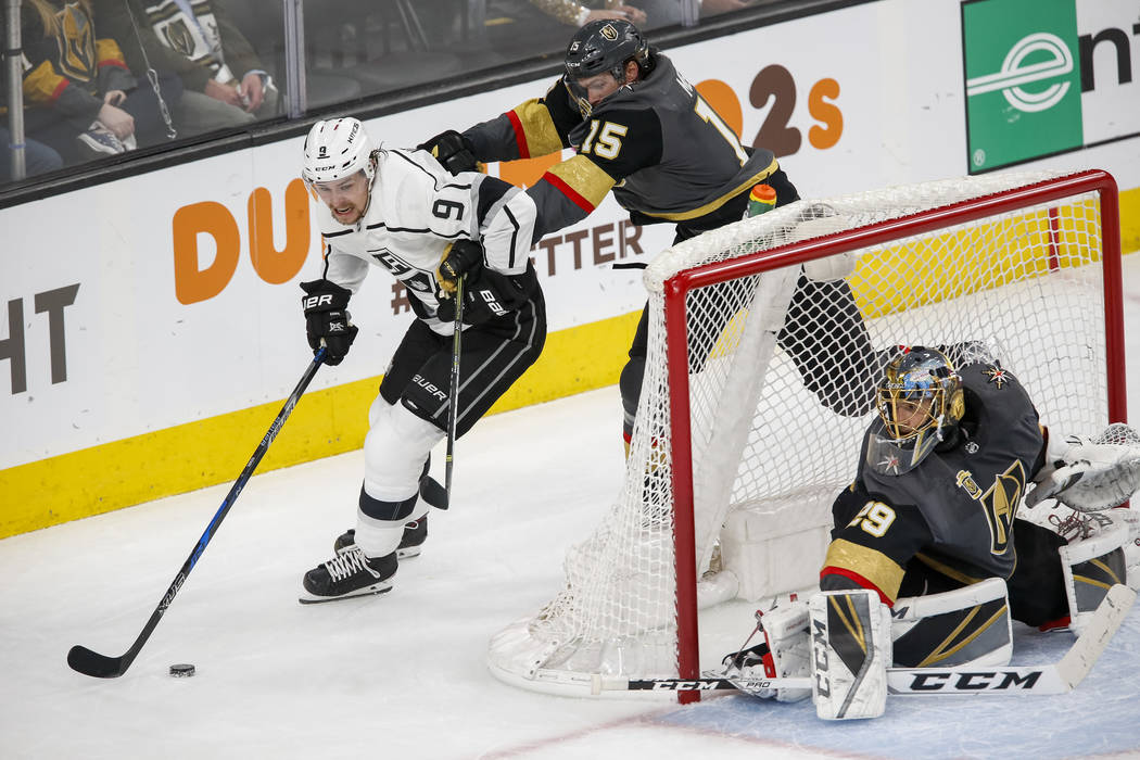 Los Angeles Kings left wing Adrian Kempe (9) is checked by Golden Knights defenseman Jon Merrill (15) as Golden Knights goaltender Marc-Andre Fleury (29) protects the net during the second period  ...