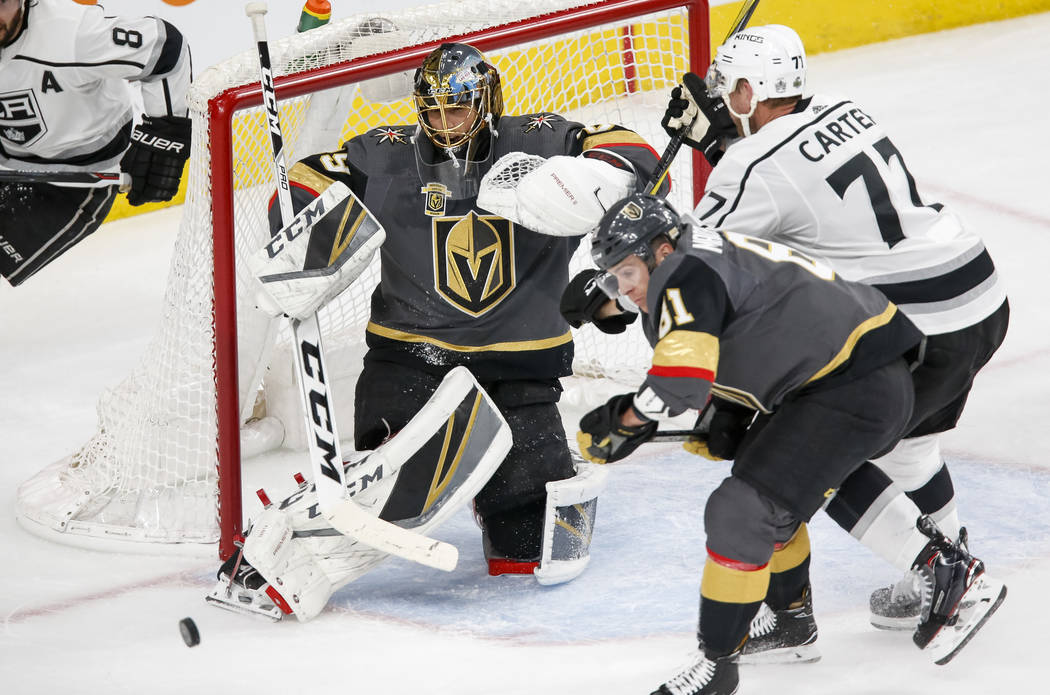 Golden Knights goaltender Marc-Andre Fleury (29) deflects a shot on goal as Los Angeles Kings center Jeff Carter (77) and Knights center Jonathan Marchessault (81) vie for the rebound during the s ...