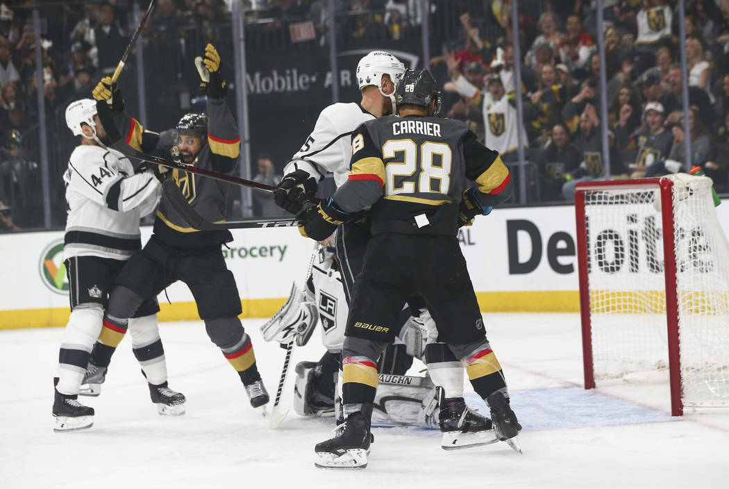 Golden Knights defenseman Shea Theodore, not pictured, scores a goal against the Los Angeles Kings as Golden Knights left wings William Carrier (28) and Pierre-Edouard Bellemare (41) look on durin ...