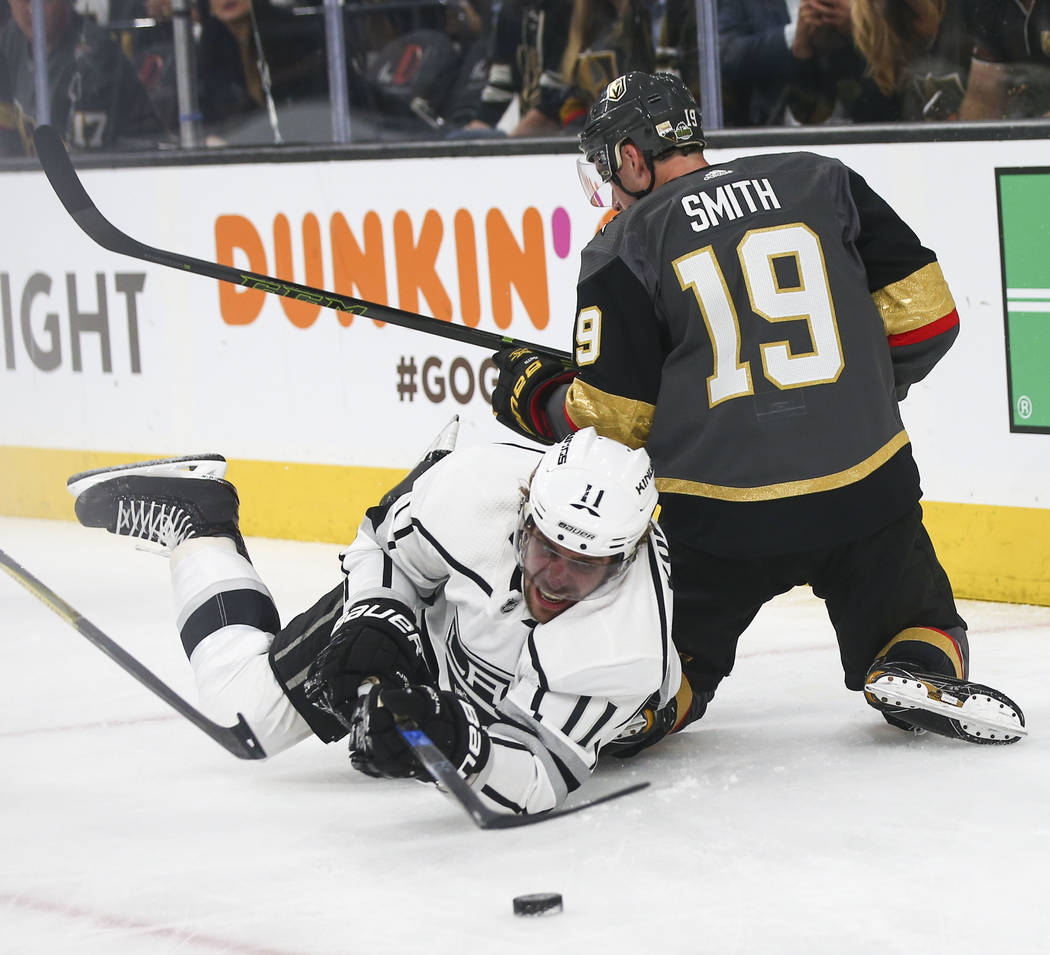 Los Angeles Kings center Anze Kopitar (11) sends the puck past Golden Knights right wing Reilly Smith (19) during the first period of Game 1 of an NHL hockey first round playoff series at T-Mobile ...