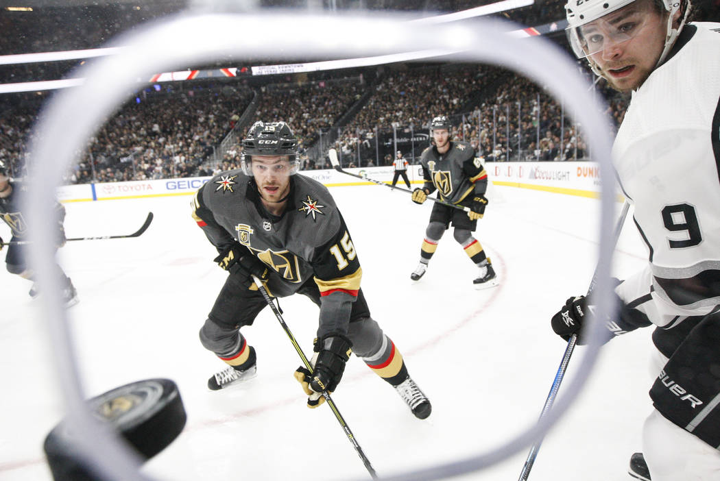 Golden Knights defenseman Jon Merrill (15) and Los Angeles Kings left wing Adrian Kempe (9) watch the puck fly by during the second period of Game 1 of an NHL hockey first-round playoff series at  ...