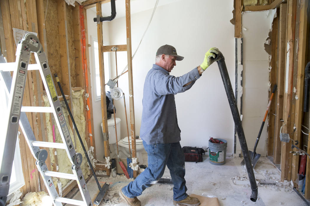 Dwight Jech, plumber with HTA Plumbing, removes pipes to make room for a bathroom remodel at the home of Ed Wiesing in Las Vegas, Thursday, April 12, 2018. Wiesing, a military veteran, underwent a ...