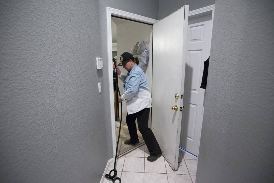 Dana Wagner, wife of military veteran Ed Wiesing, not pictured, shows how she uses a hose from a bathroom to the garage to shower her husband who recently became paralyzed from his legs, at their ...