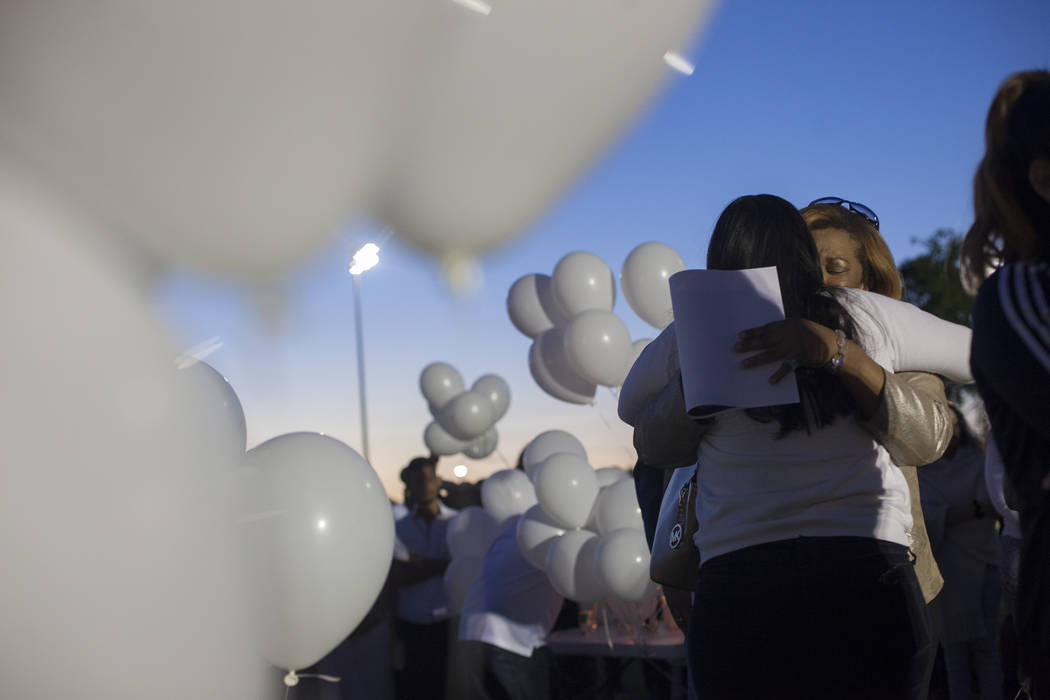 Shaja Revilla hugs Elena Pineda at a vigil for Pineda's daughter Helena Lagos in Las Vegas, Friday, April 13, 2018. Lagos and five others were killed Monday night in a fiery crash of a small plane ...