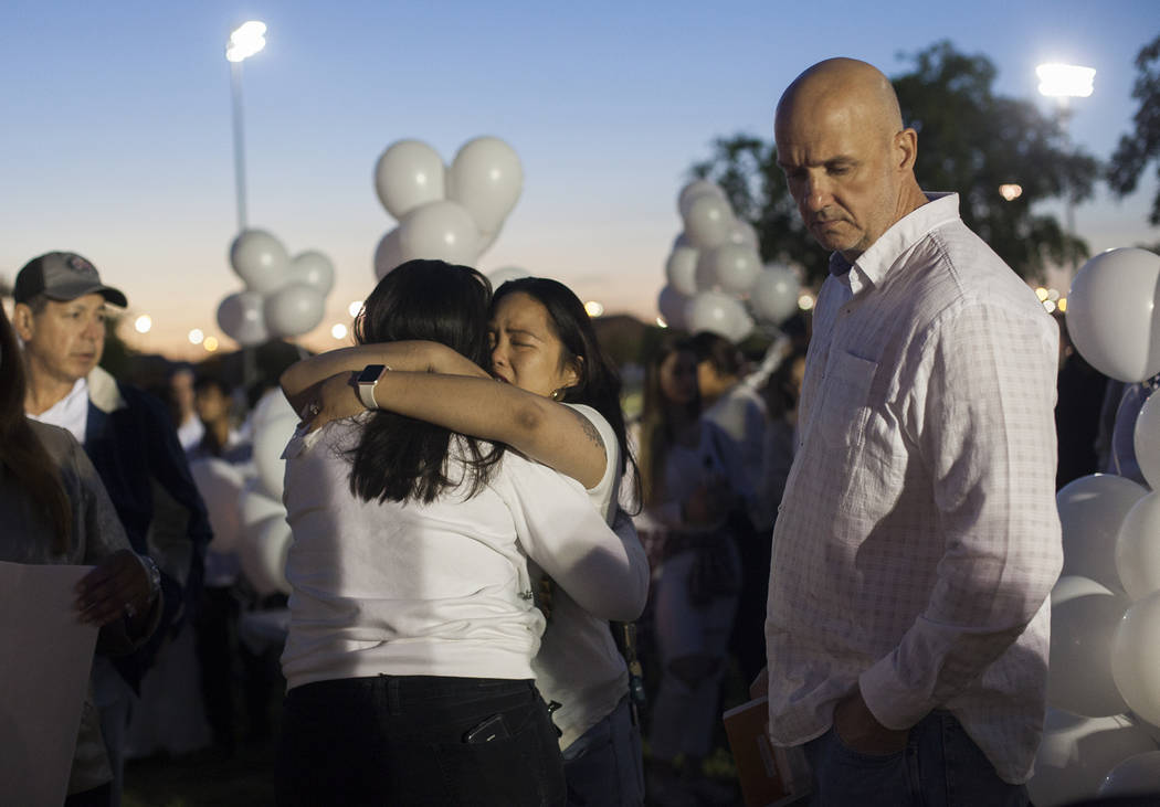 Shaja Revilla hugs Elena Pineda, the mother of Helena Lagos, next to her husband Kash Christopher, at a vigil for their daughter Helena Lagos in Las Vegas, Friday, April 13, 2018. Lagos and five o ...