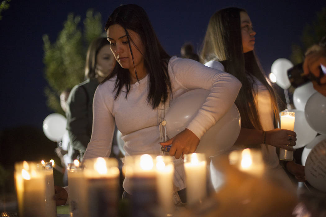Claudia Duque lights a candle at a vigil for Helena Lagos in Las Vegas, Friday, April 13, 2018. Lagos and five others were killed Monday night in a fiery crash of a small plane on a golf course in ...