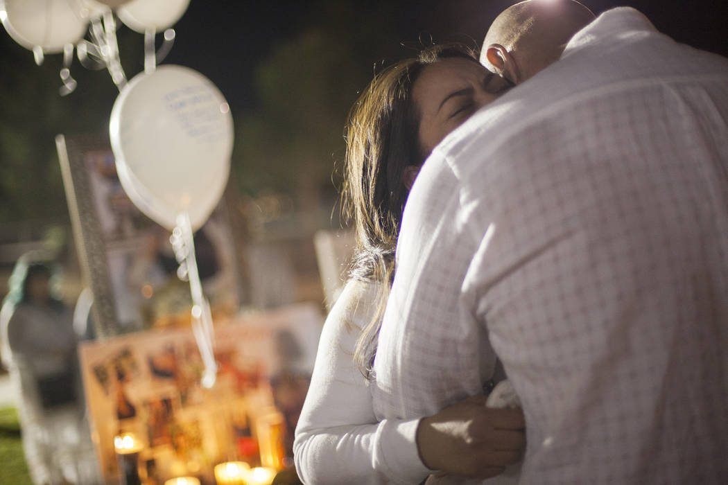 Kash Christoper hugs his wife Elena Pineda at a vigil for their daughter Helena Lagos in Las Vegas, Friday, April 13, 2018. Lagos and five others were killed Monday night in a fiery crash of a sma ...