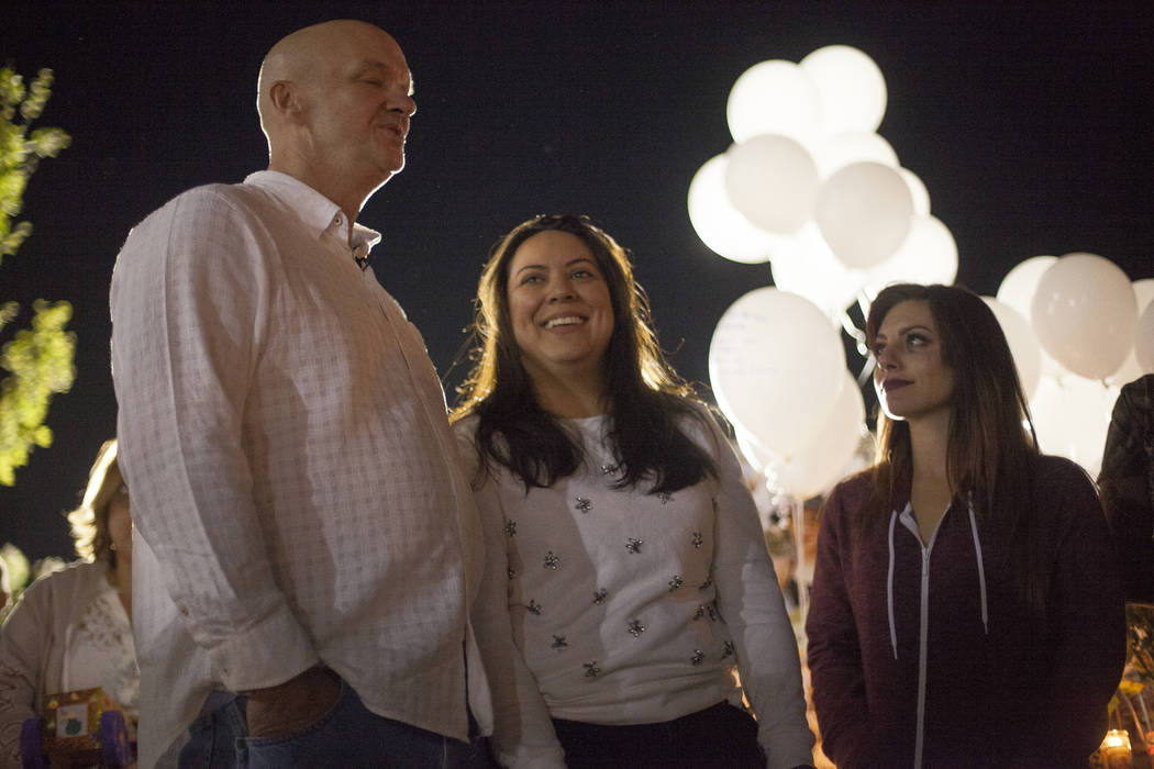Kash Christoper and his wife Elena Pineda reminisce about their daughter Helena Lagos next to family friend Amber Moriscato at her vigil in Las Vegas, Friday, April 13, 2018. Lagos and five other ...