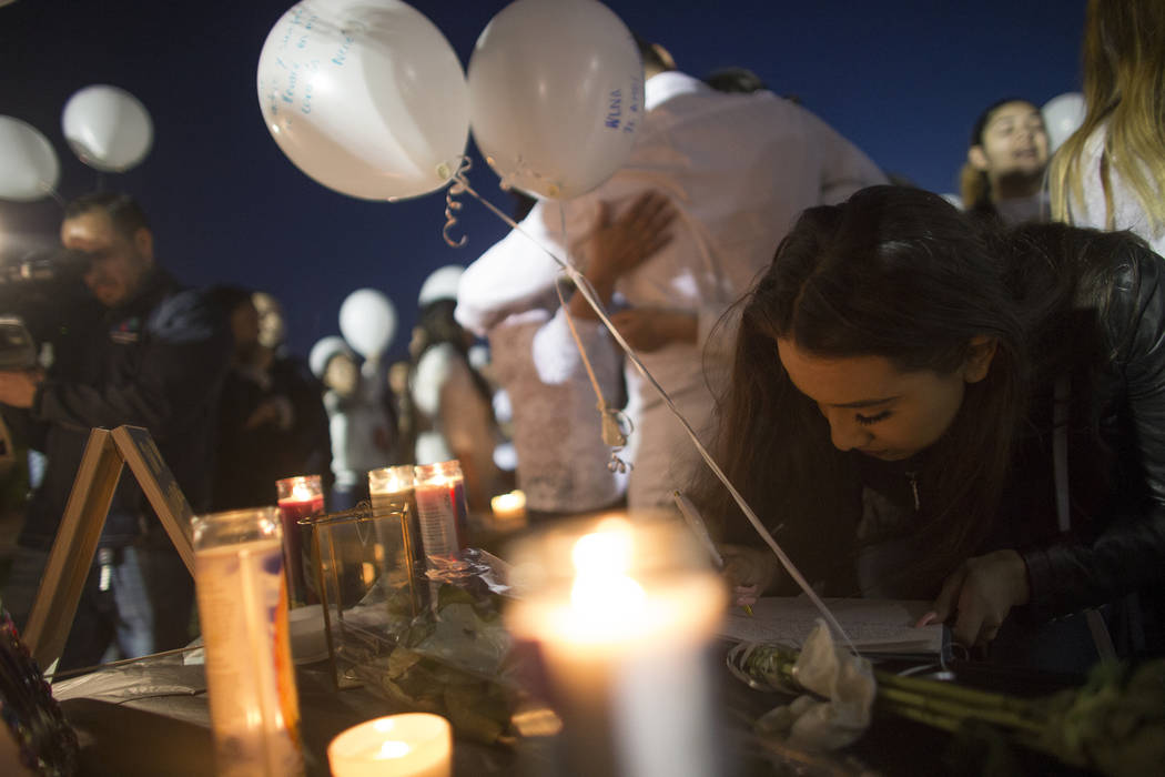 Katherine Fregozo signs a book at a vigil to honor Helena Lagos in Las Vegas, Friday, April 13, 2018. Lagos and five others were killed Monday night in a fiery crash of a small plane on a golf cou ...