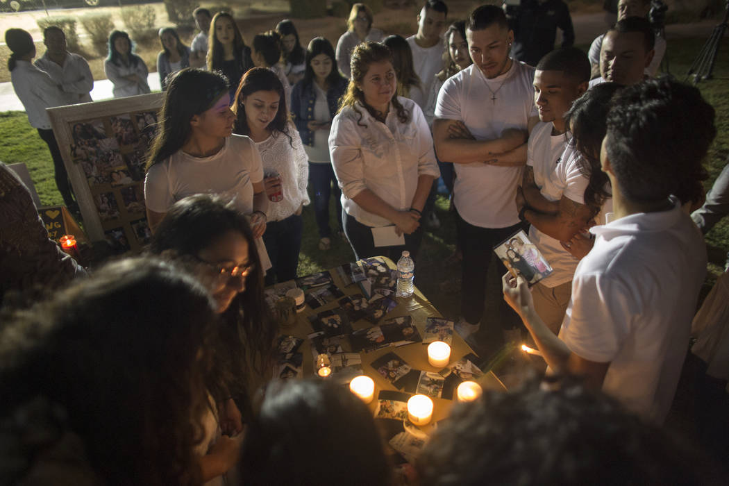 Friends and family reminisce about Helena Lagos over a table of photos of her during her vigil in Las Vegas, Friday, April 13, 2018. Lagos and five others were killed Monday night in a fiery crash ...