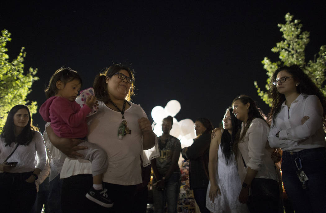 Cynthia Guzman, holding her daughter Ariana Guzman, 1, reminisces about Helena Lagos her during her vigil in Las Vegas, Friday, April 13, 2018. Lagos and five others were killed Monday night in a ...
