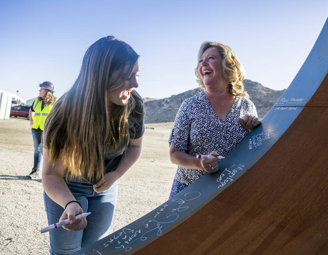 Marilyn Lee, right, wife of North Las Vegas Mayor John Lee, and her granddaughter Autumn Lueck sign a piece of the access shaft bulkhead pipe at the Southern Nevada Water Authority's low-lake-leve ...