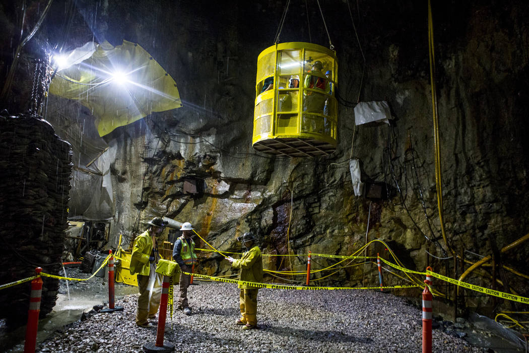 Visitors descend in a metal basket into an underground connector tunnel, part of the Southern Nevada Water Authority's low-lake-level pumping station, currently under construction at Lake Mead, on ...