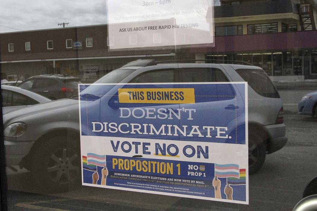 In this photo taken Monday, April 9, 2018, is a sign on a business door urging defeat of a proposition that would have rolled back protections for transgender residents in Anchorage, Alaska. Resid ...